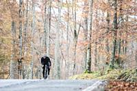 young cyclist boy riding alone at the forest in autumn. Aralar Natural Park, Navarra, Spain.