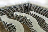 Young woman pulling books from the curved shelves library at Library at Orchard mall.