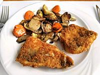 Breaded codfish with vegetables.