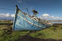 Old, derelict wooden fishing boat, left to rot on Irish coastline.