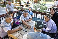 Men playing domino, chaijana, traditional tea house, in Lyabi-Hauz square, Bukhara, Uzbekistan.