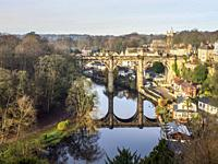 The railway viaduct reflected in the River Nidd on a sunny winter day at Knaresborough North Yorkshire England.