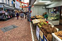 Singapore, Singapore - October 18, 2018: Food stall selling tropical fruits such as Durian in China Town. Tourists on background.