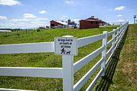 """Sign on a fence, with a farm in the background, reading """"""""All dogs must be on leash at all times""""""""."""