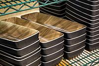 Stacks of rectangle ceramic food containers on a green metal wire rack.