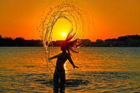 Girl flipping hair flip at sunset beach in orange sky.