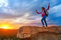 Hiker teen girl selfie smartphone on peak of mountain at sunset.