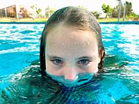 Portrait of a half submerged girl in a swimming pool.