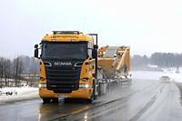 Salo, Finland - January 4, 2019: Yellow Scania R520 semi trailer of Nostokonepalvelu hauls lifting equipment on de-iced highway on a foggy day of wint...