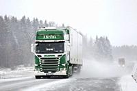 Salo, Finland - December 21, 2018: Green and white Scania R450 semi trailer and another truck on snowy rural highway in heavy snowfall in South of Fin...