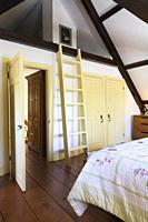 Partial view of the king size bed and old wooden ladder leading to the attic in the master bedroom on the upstairs floor inside an old reconstructed 1...