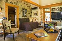Antique upholstered chair and wooden coffee table in the new extension inside an old circa 1740 Canadiana fieldstone cottage style, Quebec, Canada.
