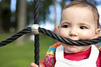 11 month baby girl bitting playground rope as it was a teether. Biting and Teething for babies concept.