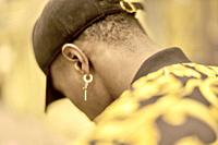 back view of man wearing golden earring, jewelry, in Munich, Germany