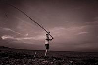 Fisherman throwing the fishing rod, Alcocebre, Castellon province, Valencian Community, Spain