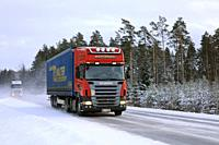 Salo, Finland - January 18, 2019: Red Scania R420 semi trailer Marjamaki and another truck drive on snowy winter highway in South of Finland.