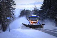 Salo, Finland - January 18, 2019: Blue Scania truck equipped with snowplow clears a snowy bus stop by the highway in South of Finland at winter dusk.
