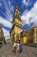 Three women in traditional andalusian costume by the Great Mosque, Cordoba, Andalusia, Spain