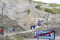 Road sign at the exit of the city of Cuenca, hikers in background, Castile-La Mancha, Spain