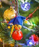 Small Christmas oraments hanging on a Christmas tree.
