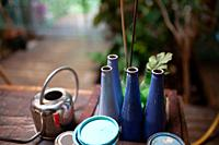 Closeup of bottles painted in blue in a studio of artist.