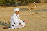 India, Rajasthan, Jodhpur region, Bishnoi devotee in meditation before a wild Chinkara (Indian gazelle). .
