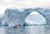 Icebergs in the Disko Bay, local hunter hunting for seal in small boat. Greenland, Denmark, August.