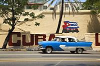 Old American car at the street in front of the wall paintings at Vedado district, Havana, La Habana, Cuba, West Indies, Central America