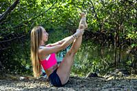 Young woman doing a yoga pose (Modified Boat Pose - Navasana) in a natural setting - Fort Lauderdale, Florida, USA.