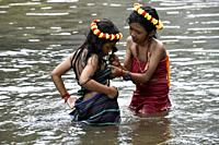 Two young girls wearing flower garland on head in Bou Sra waterfall near Sen Monorom, Mondolkiri province, Cambodia, South east Asia.
