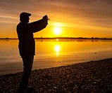 Man taking a picture at sunset, Borgarnes, Western Iceland.