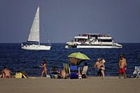People walking along the beach with boats in the background. Almeria, Spain.