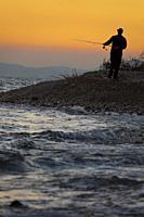 Fisherman fishing on the beach, Alcocebre, Castellon, Spain.