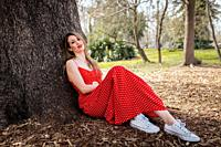 Young smile blond woman sitting near tree with red long dress.