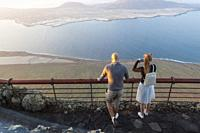 Young couple watching the abyss. Mirador del Rio, Lanzarote. Spain.