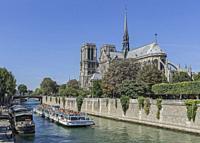Bateau-Mouche tour boat on the Seine river with Notre-Dame-de-Paris cathedral in the background, Paris, France.