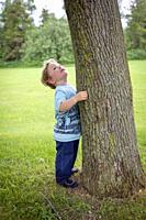 Toddler hugging a tree.