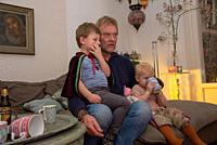grandfather with grandchildren watching tv.
