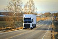 Salo, Finland - March 1, 2019: White Volvo FH truck double trailer for Posti Group, Finnish postal service on highway at sunset time in early spring.