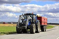 Ilmajoki, Finland - August 11, 2018: Blue Valtra farm tractor pulls trailer load of harvested grain along rural road on a clear day of autumn harvest.