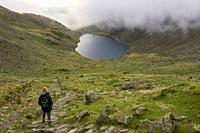 A fell walker looks over Goat's Water between The Old Man of Coniston and Dow Crag in the Lake District National Park, Cumbria, England.