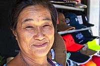 Local Vietnamese woman selling caps from a street stall near the local market, Ho Chi Minh City, Vietnam, Asia.
