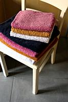 Interior scene, stack of folded towels on vintage white chair