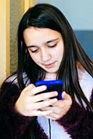 girl looks at the smartphone-portrait of absorbed little girl in the phone screen.