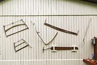 Antique saws, pitchfork and other hand tools hanging on the side wall of old grey painted wooden planked barn