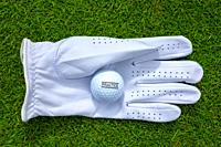 Golf Glove and Ball on the Green Grass in Switzerland.