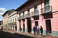 People walking in front of colorful colonial buildings with balconies at the historic center, Quito, Ecuador, South America