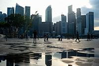 Singapore, Republic of Singapore, Asia - People at the waterfront promenade in Marina Bay with the city skyline of the central business district in th...
