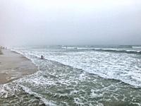Mist-shrouded coastline as the tide recedes with a handfull of surfers in the distance. Cape Town, Soth Africa. Surfers can be seen in the far distanc...