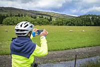 A woman takes a photo on the Central Otago Rail Trail, South Island, New Zealand.